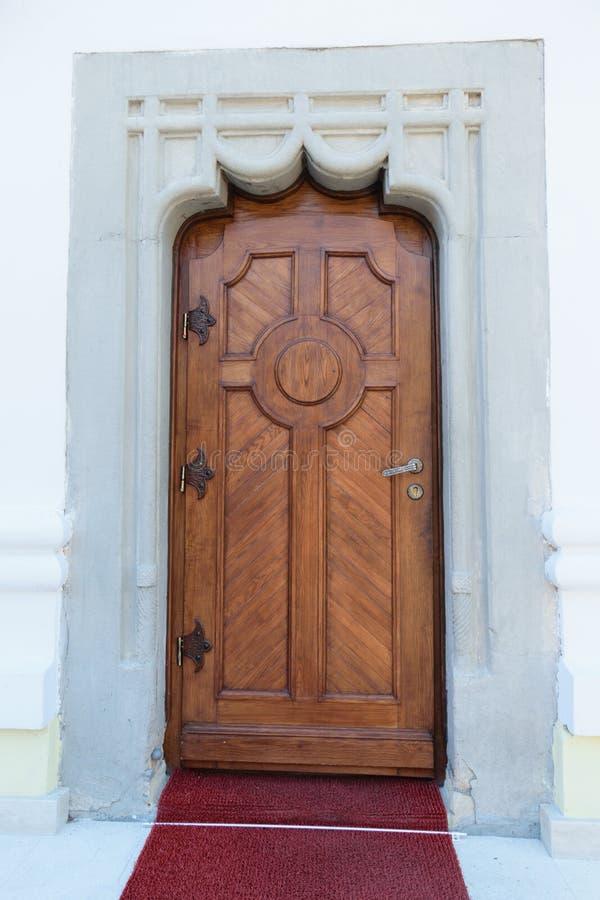 Porta di legno massiccia, mura di cemento artistici ed entrata del tappeto rosso fotografie stock