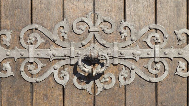 Porta di legno pesante con l'ornamento di metallo complesso fotografie stock