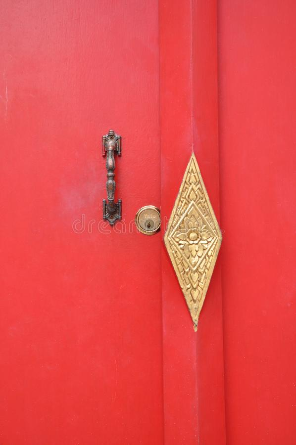 Porta di legno rossa del tempio con i montaggi d'ottone decorati fotografia stock