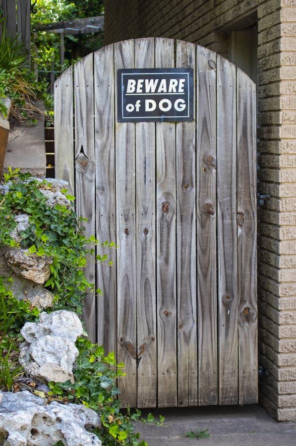 Porta di legno rustica incurvata ai punti e giardino con attenti al cane il segno fotografia stock