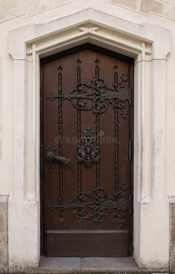 Porta di legno scolpita con la manopola fatta a mano ed il bello pezzo fucinato del metallo immagine stock libera da diritti