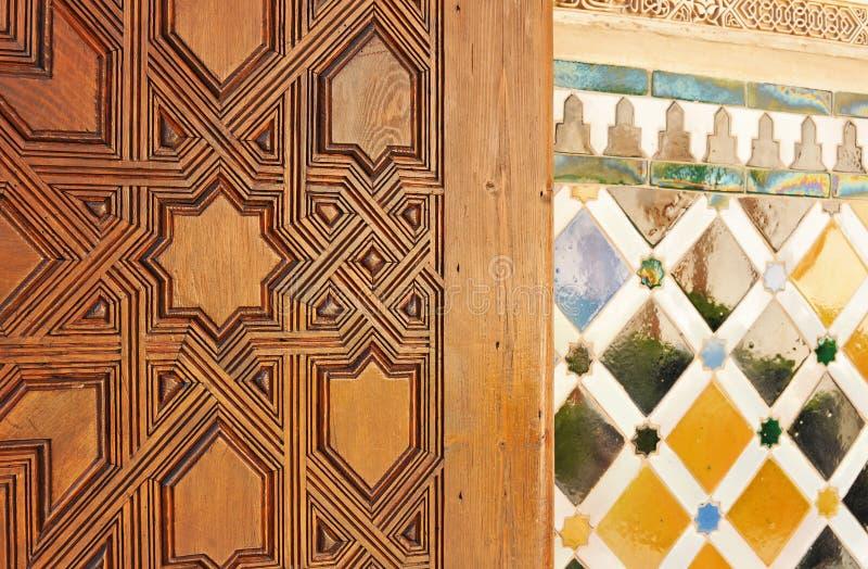 Porta di legno scolpita e mosaico delle mattonelle con stile islamico Palazzo di Alhambra a Granada, Andalusia, Spagna immagine stock