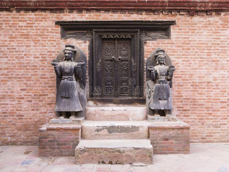 Porta di legno scura pienamente scolpita nello stile nepalese tradizionale con due belle statue a grandezza naturale fotografie stock