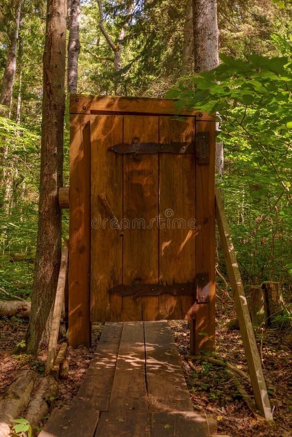 Porta di legno su un modo della passeggiata attraverso la foresta immagini stock libere da diritti
