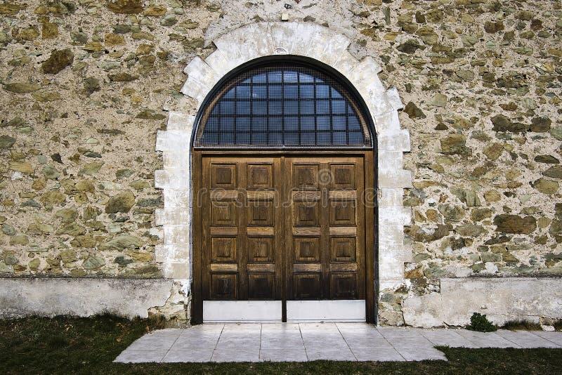 Porta di legno sulla chiesa della parete di pietra immagini stock
