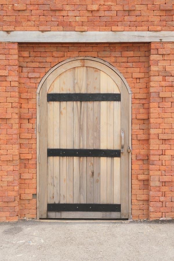 Porta di legno in un muro di mattoni immagini stock