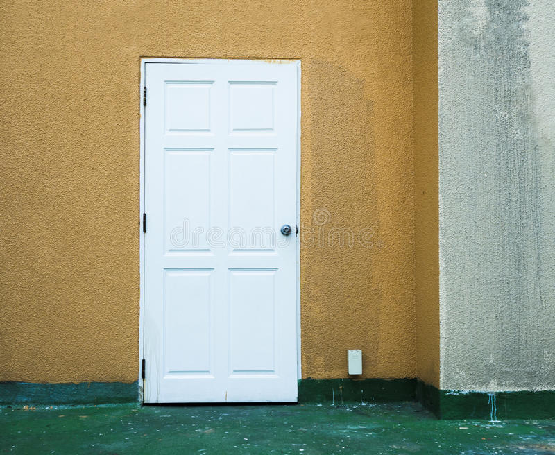 porta di uscita bianca sulla parete gialla immagini stock