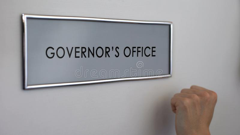 Porta do escritório do regulador, mão que bate o close up, visita ao administrador público, autoridade fotos de stock