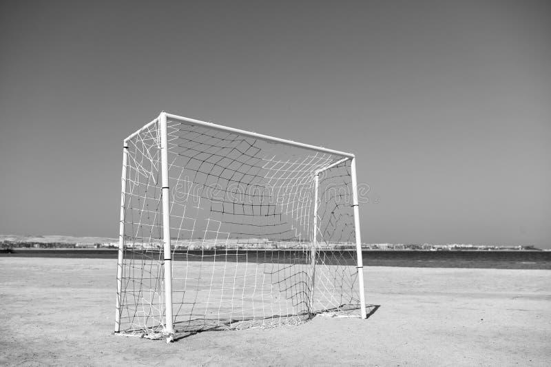 A porta do futebol ou do futebol com rede no céu azul e no mar da praia da areia ajardina o fundo Conceito do entretenimento do r imagens de stock royalty free