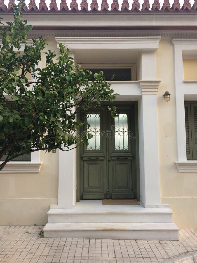 A porta do verde da entrada à casa Uma árvore de mandarino cresce quase foto de stock royalty free