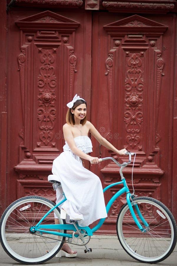 Porta do vintage na cidade velha na menina do primeiro plano na bicicleta foto de stock