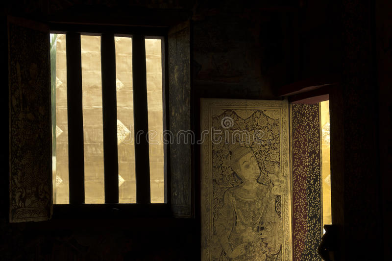 Porta dorata con luce ed ombra in tempio di Chiang Mai, Tailandia immagini stock