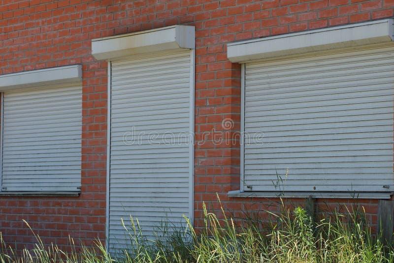 A porta e as janelas são fechadas pelos rolos brancos em uma parede de tijolo marrom foto de stock royalty free