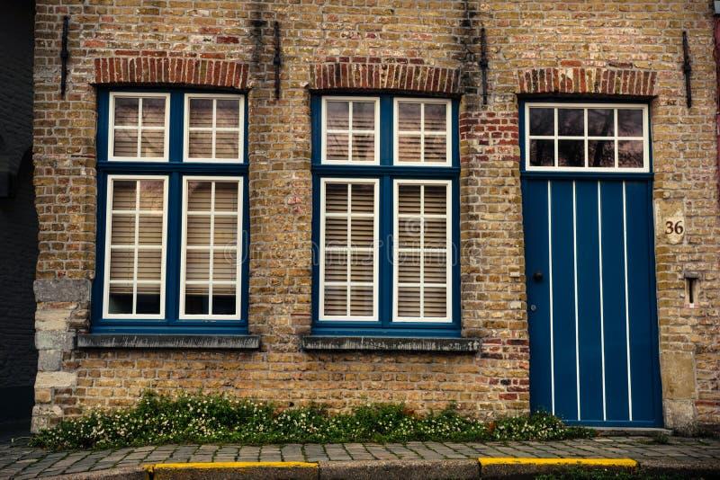 Porta e finestre di legno blu sul muro di mattoni della casa a Bruges, Belgio fotografia stock libera da diritti