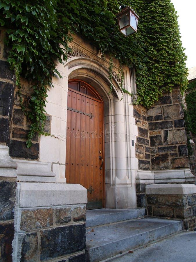A porta e a hera de madeira cobriram o edifício de pedra imagem de stock