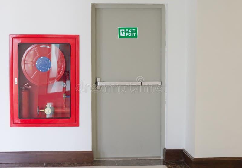 A porta e o fogo da saída de emergência extinguem o equipamento imagem de stock