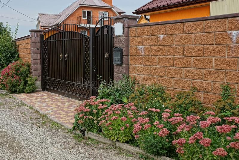 A porta e o tijolo do metal de Brown cercam perto das plantas verdes e das flores decorativas fotografia de stock royalty free