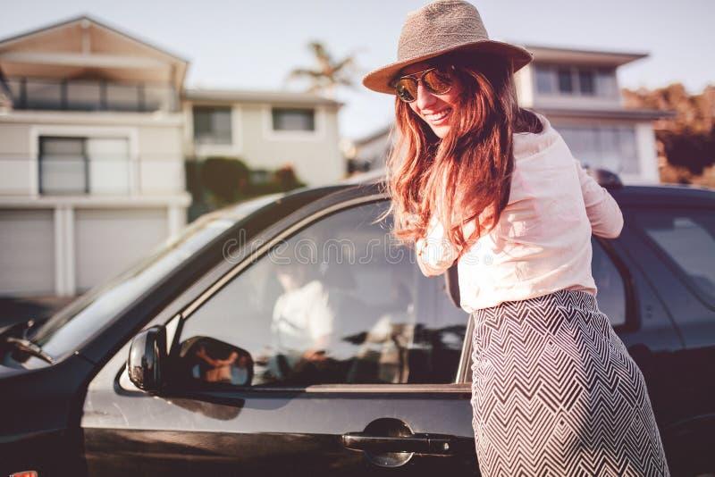 Porta ed esame di automobile sorridente di apertura della donna della macchina fotografica Concetto di avventura di viaggio strad fotografia stock libera da diritti