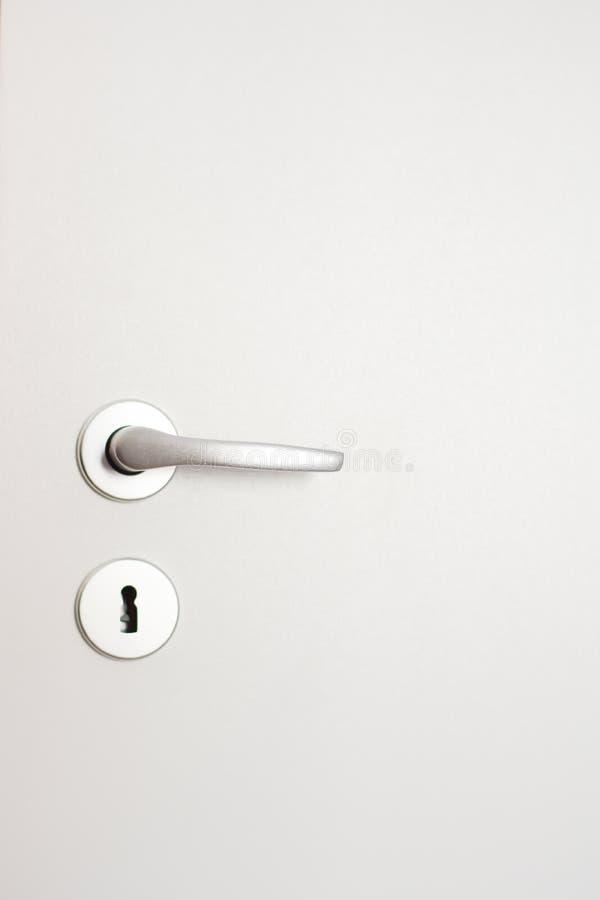 Porta fechado branca com o puxador de prata no fundo branco da parede imagem de stock royalty free