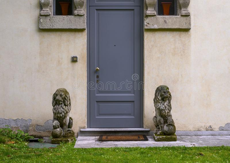 Porta fiancheggiata dalle statue del leone del guardiano nel giardino della Camera di Atellani, Museo Vigna di Leonardo, Milano fotografia stock libera da diritti