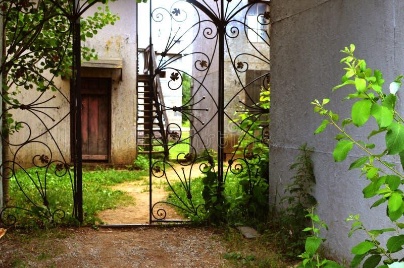 A porta forjada velha em um jardim imagens de stock royalty free
