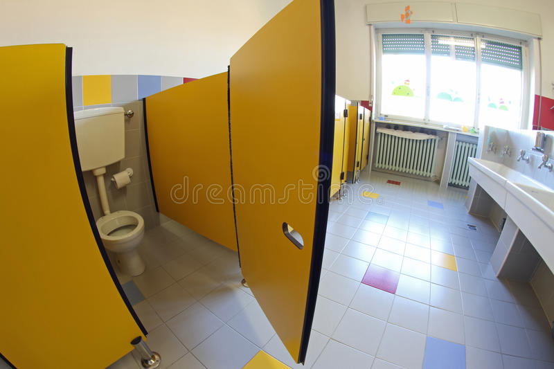 Porta gialla nei bagni con i lavandini di una scuola materna fotografia stock libera da diritti