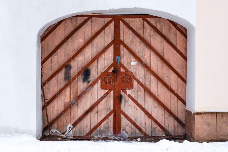 Porta grande de madeira velha Entrada com uma porta dobro arqueada, feita da madeira com quadro do metal fotografia de stock royalty free
