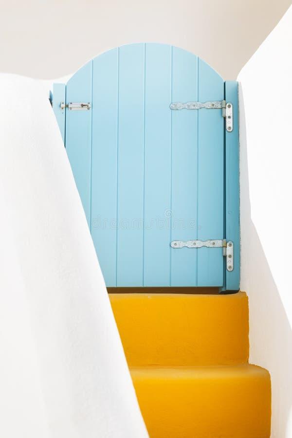 Porta grega azul pequena e etapas amarelas na ilha de Santorini, Grécia fotografia de stock