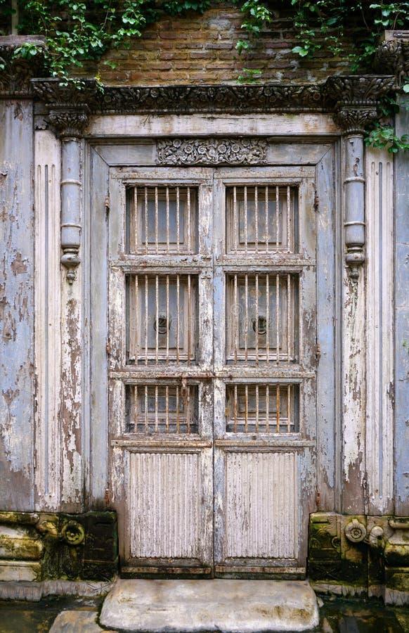 Porta grigia di legno d'annata antica con la porta d'acciaio bianca della griglia fotografia stock
