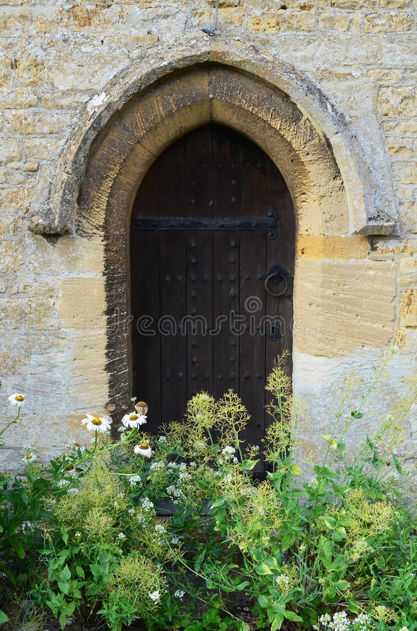 Porta lateral da igreja com flores selvagens fotos de stock