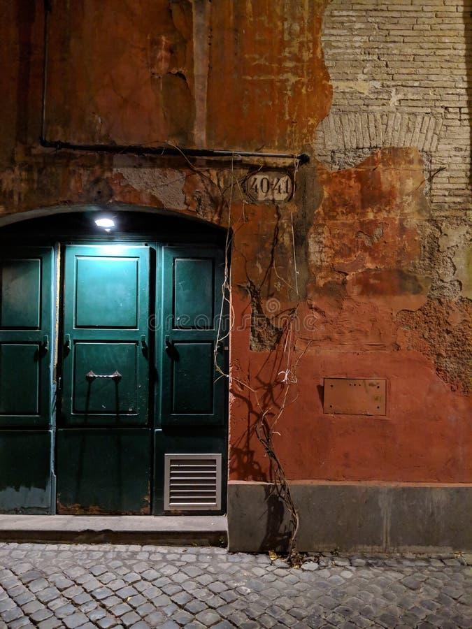 Porta leggera a vecchia costruzione a Roma alla notte fotografia stock