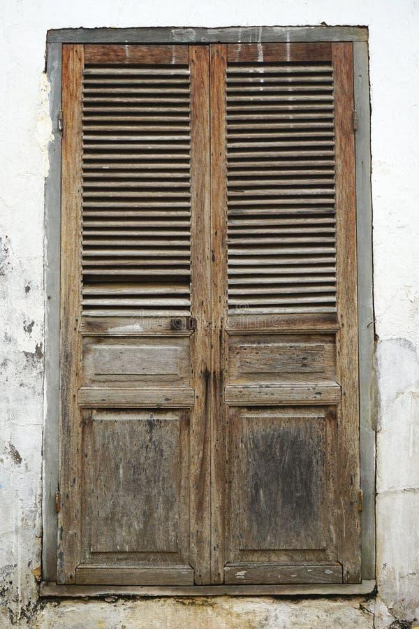 Porta louvered di legno stagionata messa in una parete di sbriciolatura antica dello stucco fotografia stock libera da diritti