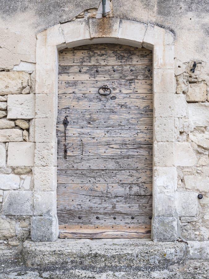 Porta medieval de madeira grossa muito velha na parede antiga da pedra calcária fotos de stock royalty free