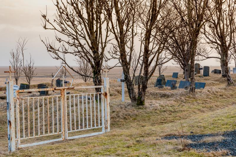 Porta no cemitério da igreja de Kalfafellsstadur em Islândia com cruzes, lápides e grama longa fotografia de stock royalty free