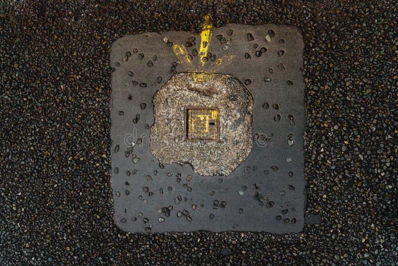 Porta pequena do metal com um furo para uma chave e uma seta amarela em um pavimento escuro imagem de stock