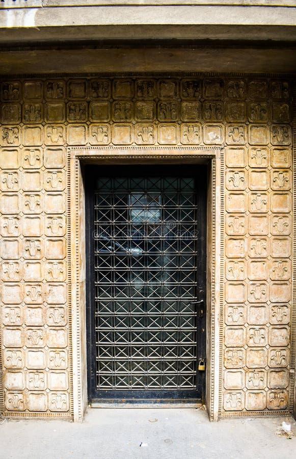 Porta preta do ferro velho travada com detalhes antigos Porta da rua fechado envelhecida na construção barroco do estilo arquitet imagens de stock