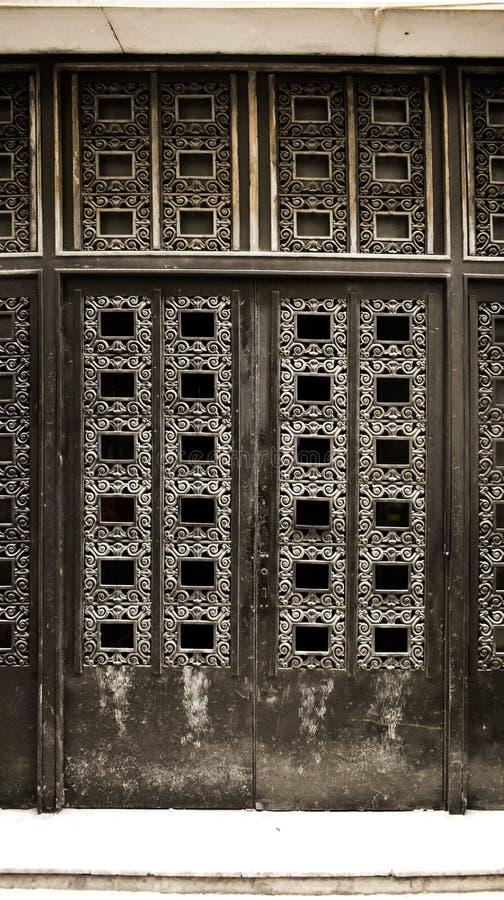 Porta preta do ferro velho travada com detalhes antigos Porta da rua fechado envelhecida na construção barroco do estilo arquitet fotos de stock royalty free