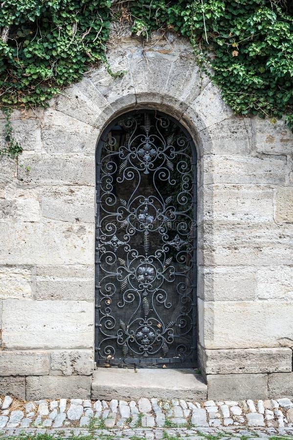 Porta preta medieval velha do metal com barra cerved e fotos de stock