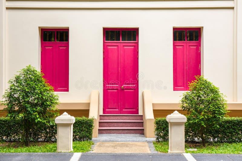 porta rosa, finestra rosa sulla parete crema sulla scala rosa con lo sma fotografia stock libera da diritti