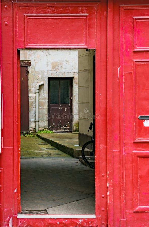 Porta rossa chiara che si apre in un cortile interno con un'altra porta fotografia stock libera da diritti