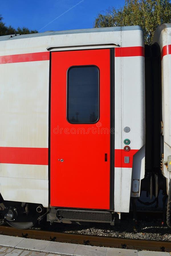 Porta rossa di un trasporto bianco del treno passeggeri sul binario un giorno, fuori della vista immagine stock libera da diritti