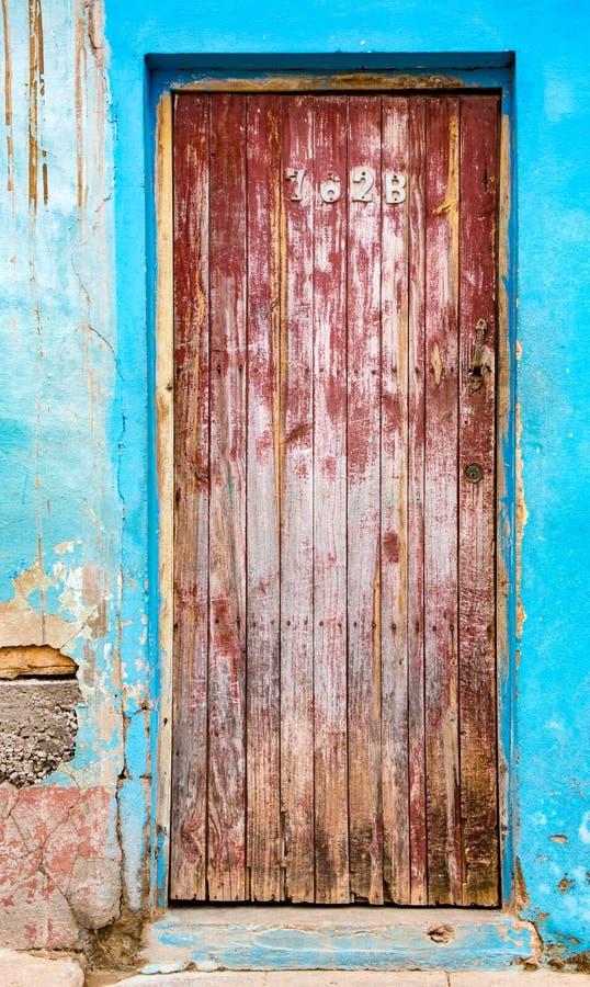 Porta rossa sbiadita sul muro di mattoni blu con gesso rotto immagine stock