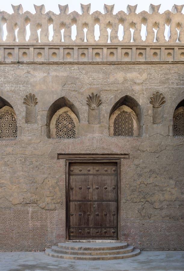 Porta stagionata di legno, finestra perforata dello stucco decorata con i modelli floreali e tre punti sulla parete di mattoni di fotografia stock