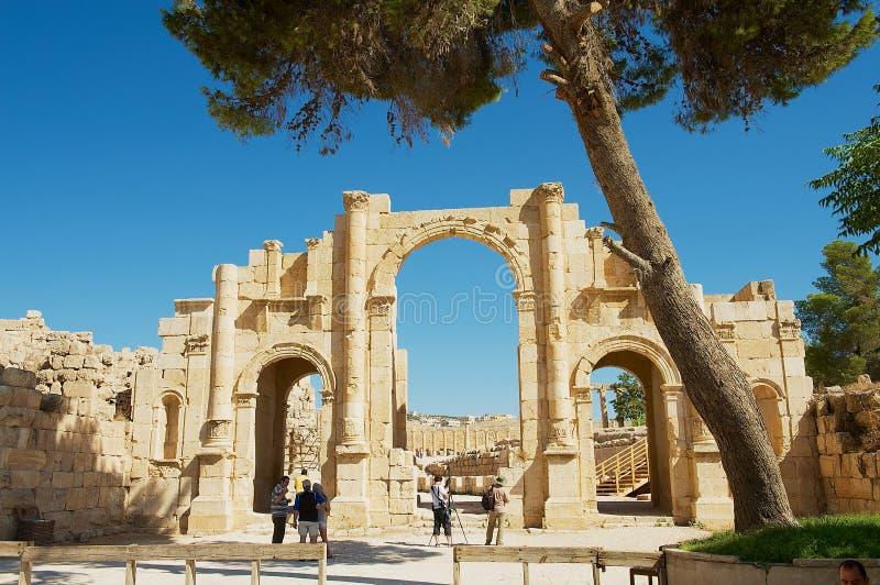 Porta sul da visita dos turistas da cidade romana antiga de Gerasa, Jerash moderno em Jordânia imagens de stock