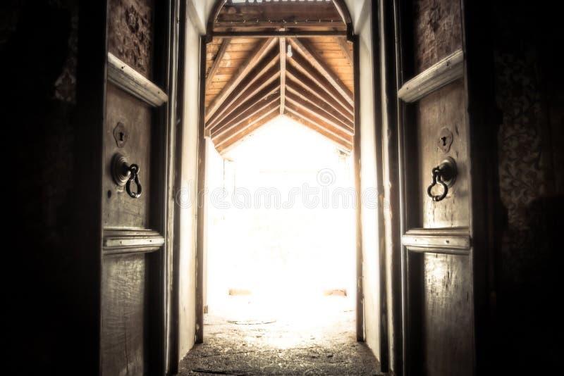 Porta velha aberta da porta do templo antigo com luz do esplendor com efeito da luz na extremidade do túnel fotos de stock