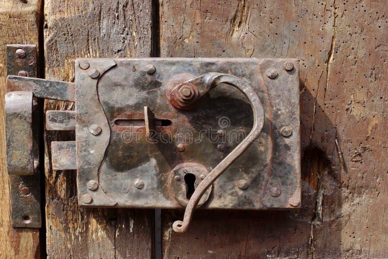 A porta velha com entalha um encaixe no fechamento e o puxador fotos de stock royalty free