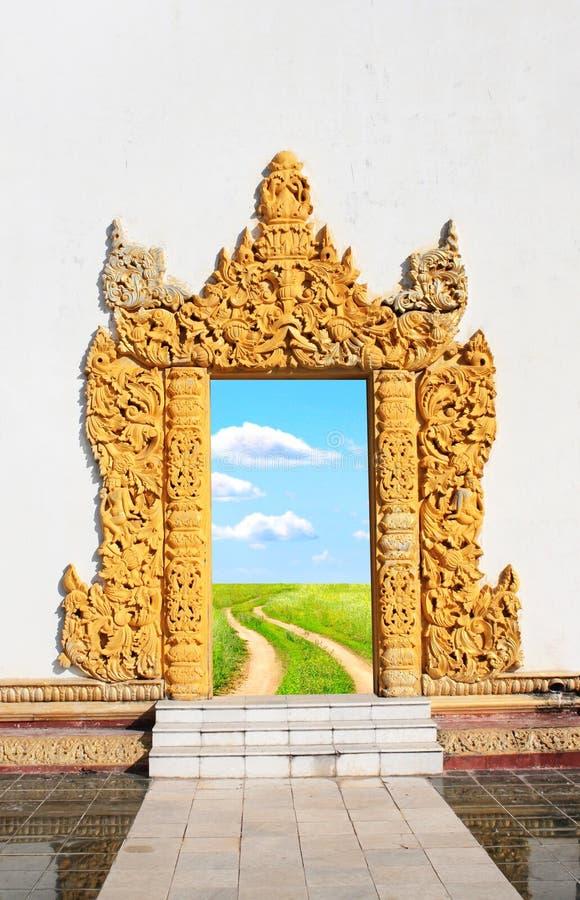 Porta velha com fachada de madeira e estrada no prado verde imagem de stock royalty free