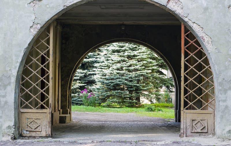 Porta velha do metal na parede e passagem ao jardim fotos de stock royalty free