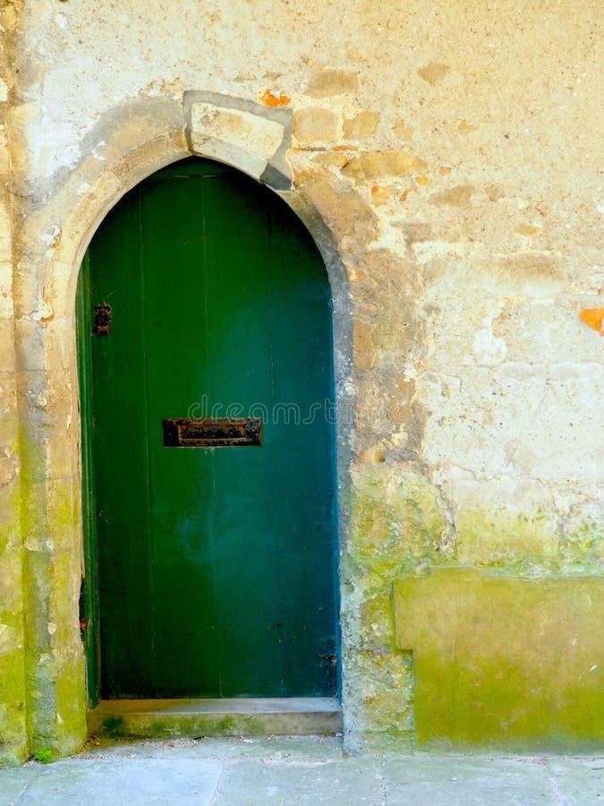 Porta verde medieval e parede de pedra imagens de stock