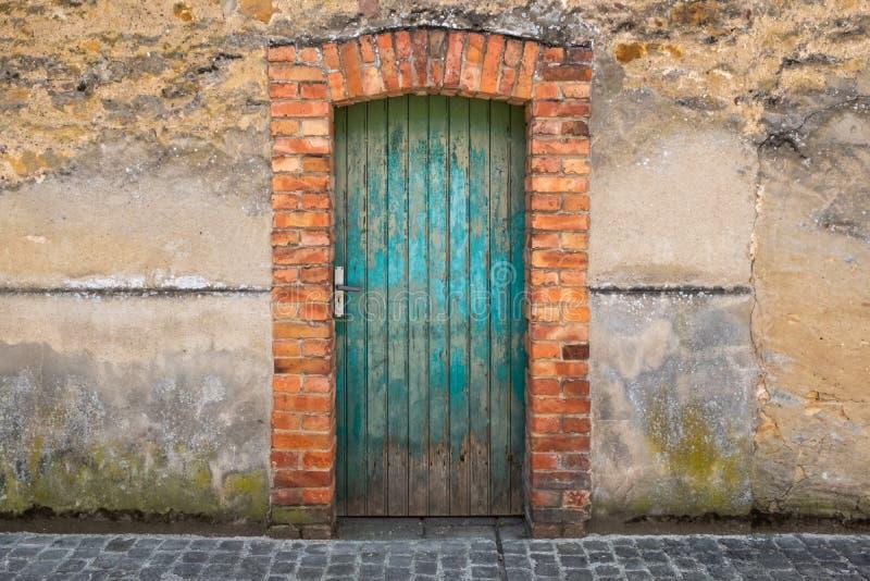 Porta verde velha com um arco do tijolo vermelho fotos de stock royalty free